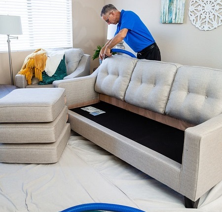 Technician Cleaning White Sofa